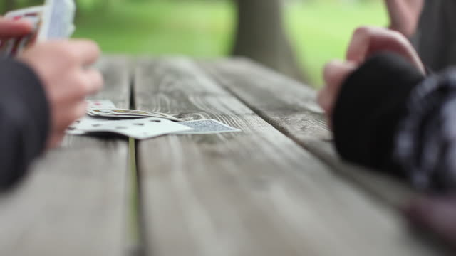 cu selective focus hands of teenagers (14-15, 16-17) playing cards at picnic table / cazenovia, new york, usa - female with group of males stock videos & royalty-free footage