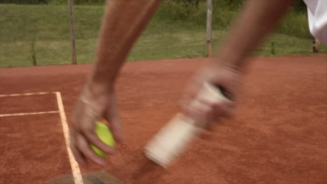 hands of tennis serve close up on red clay - ボール点の映像素材/bロール