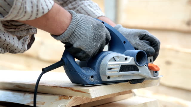 hands of the builder planing a piece of a wooden plank. - protective glove stock videos and b-roll footage