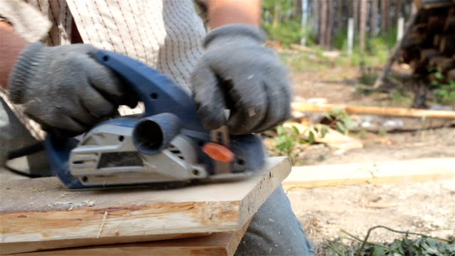 Hands of the builder planing a piece of a wooden plank.