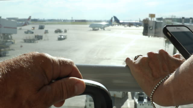 hands of travellers overlooking tarmac, at airport - handle stock videos & royalty-free footage