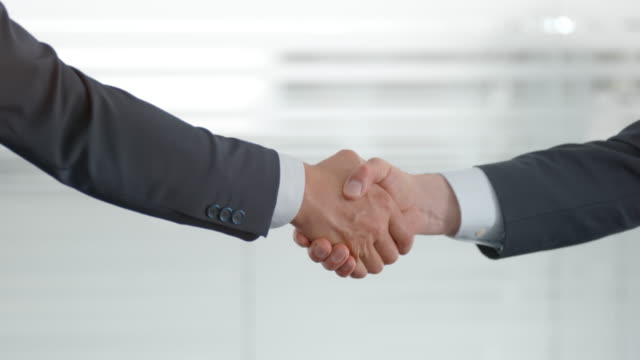 hands of two businessmen doing a handshake - part of a series stock videos & royalty-free footage