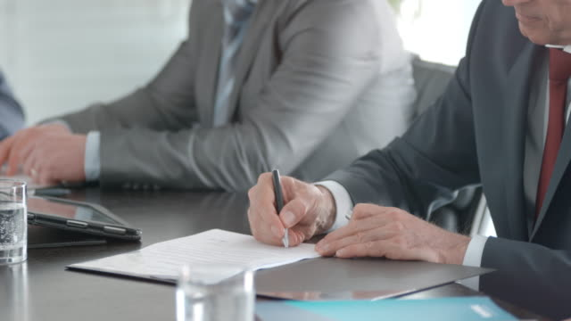 vídeos de stock e filmes b-roll de hands of two businessmen sitting opposite each other, signing the contract and shaking hands in front of colleagues - contrato