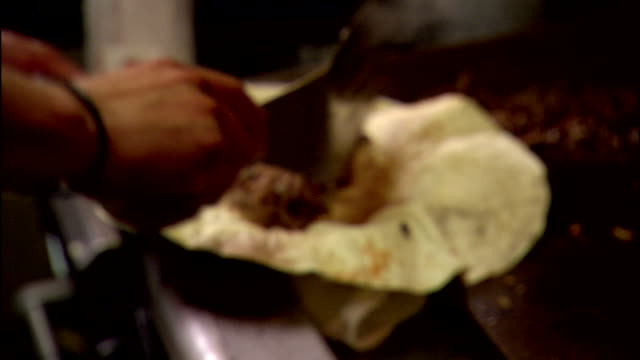hands of unidentifiable male chef using metal turner to scoop ground meat off commercial grill & onto large tortilla w/ refried beans, inside kitchen... - tortilla flatbread stock videos & royalty-free footage