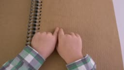 hands of Visually impaired child read braille book with characters font