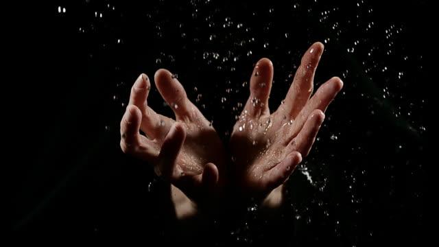 vidéos et rushes de hands of woman and water against black background, slow motion 4k - rafraîchissement