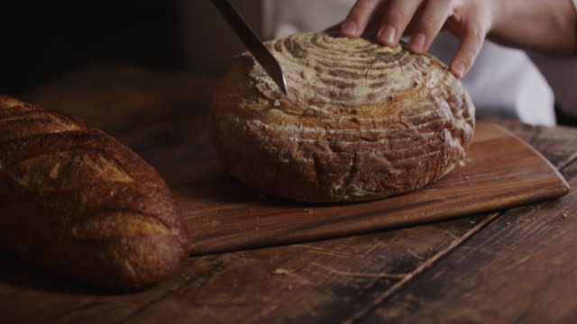 hands of woman cutting loaf of fresh bread on cutting board / cedar hills, utah, united states - loaf stock videos & royalty-free footage