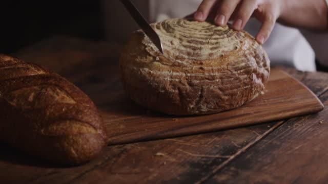 Hands of woman cutting loaf of fresh bread on cutting board / Cedar Hills, Utah, United States