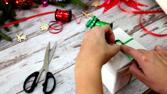 händerna på kvinna dekorera jul presentbox - förpackning bildbanksvideor och videomaterial från bakom kulisserna