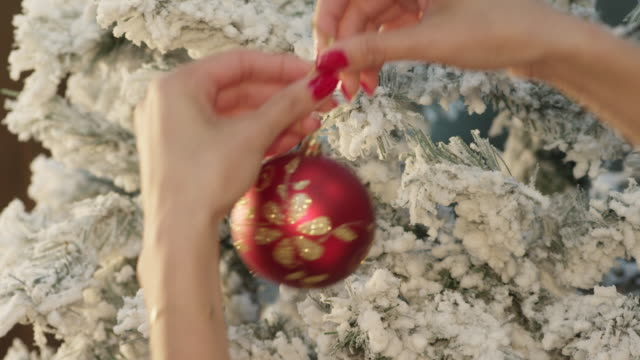 ECU hands of woman decorating Christmas tree with one red bauble