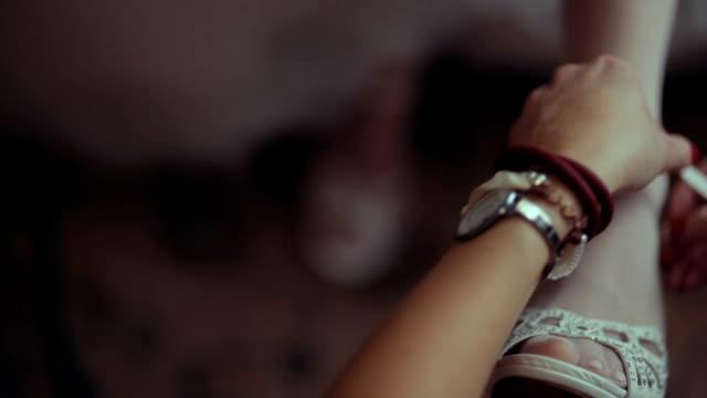 CU SELECTIVE FOCUS Hands of woman fastening shoe on bride's foot