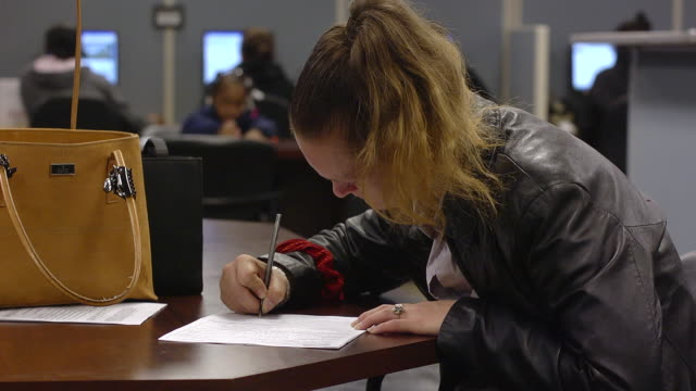 vídeos de stock e filmes b-roll de ms hands of woman filling out forms seeking job at state run job center / jackson, michigan, united states  - desemprego