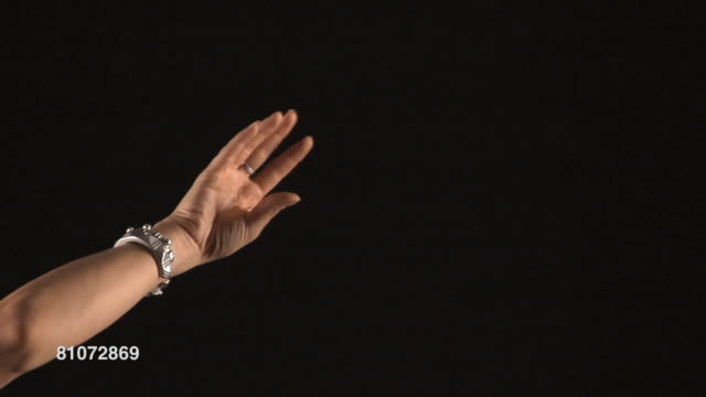 MS Hands of woman moving in Indian mudras against black background/ San Rafael, California