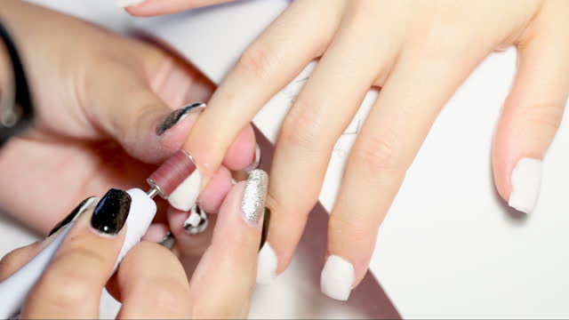 hands of woman receiving manicure - sich verschönern stock-videos und b-roll-filmmaterial