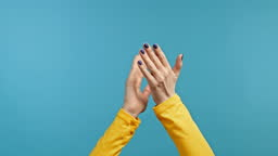 Hands of woman, she is very glad, she claps hands because of excellent news. Lady applauding on blue background