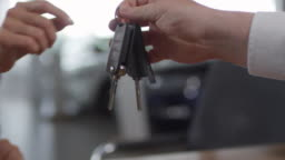 Hands of Woman Taking Car Key from Auto Dealer
