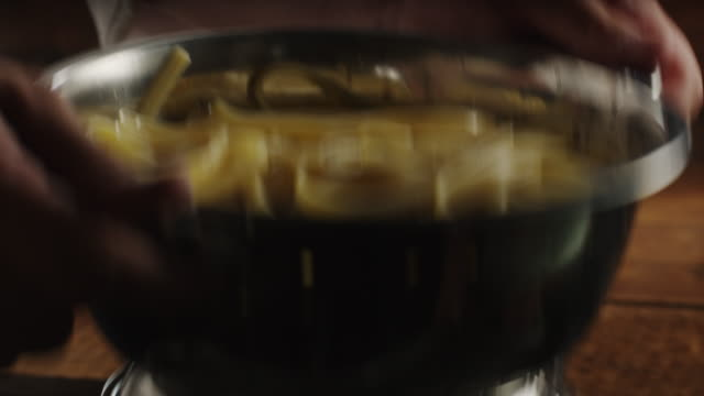 Hands of woman tossing hot pasta in colander / Cedar Hills, Utah, United States