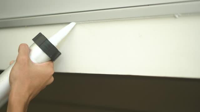 mani del lavoratore che usa un caulk per riparare la finestra esterna - sigillante video stock e b–roll