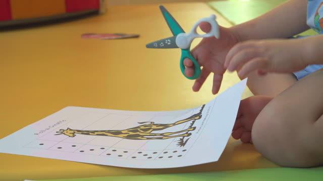 vídeos de stock, filmes e b-roll de 4k: mãos de garoto aprender a cortar usando tesoura pequena. - tesoura