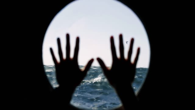 hands on the porthole during a gale at sea - marinaio video stock e b–roll