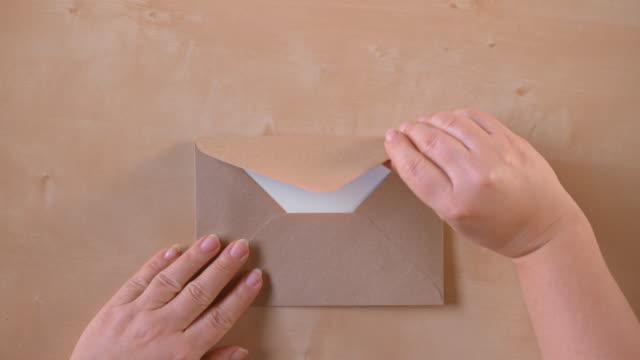 slo mo ld hands opening a brown envelope and taking out a sheet of paper - correspondence stock videos & royalty-free footage
