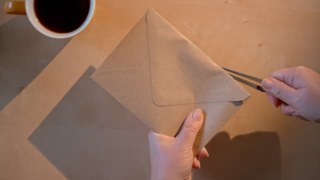 slo mo ld hands opening a brown envelope with a knife - brown stock videos & royalty-free footage