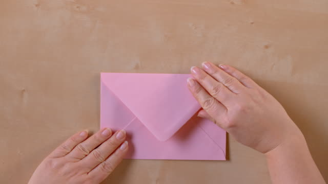 slo mo ld hands opening a pink envelope and taking out a sheet of paper - correspondence stock videos & royalty-free footage
