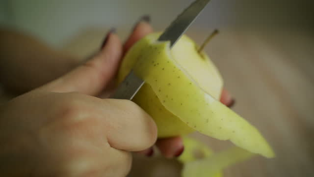 stockvideo's en b-roll-footage met handen die een groene appel op een houten raad schillen - pellen
