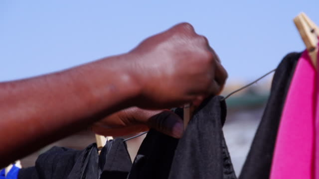 stockvideo's en b-roll-footage met cu hands pegging washing onto washing line / cosmo city, south africa - wasknijper