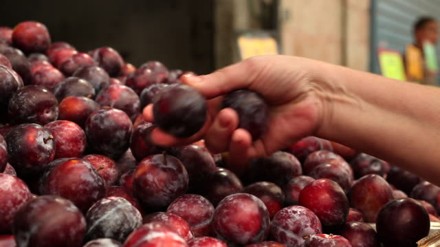 Hands pick out ripe plums at the Ben Yehuda Market in Jerusalem.