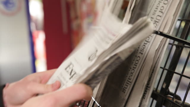 vídeos de stock e filmes b-roll de hands pick up and put back down a daily newspaper from a rack outside a uk newsagent. - jornal