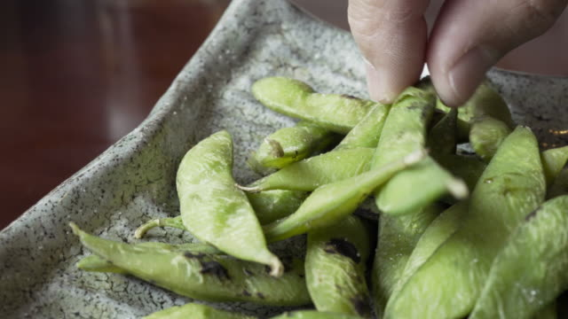 hands picking edamame green soybeans, japanese food - plant pod stock videos & royalty-free footage