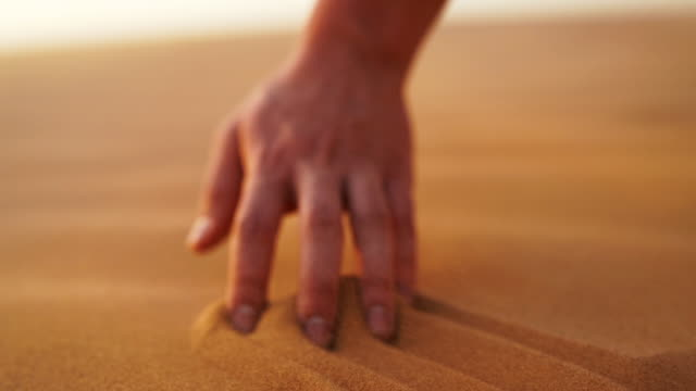vidéos et rushes de hands picking up sand in the desert - focus concept