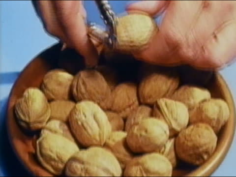 1962 hands picking walnut from bowl and cracking shell with nutcracker to reveal seed / AUDIO