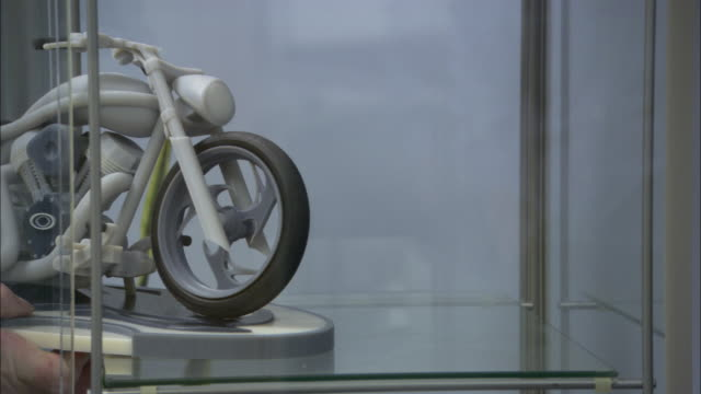 hands place a scale model motorcycle into a glass case. - skåp med glasdörrar bildbanksvideor och videomaterial från bakom kulisserna
