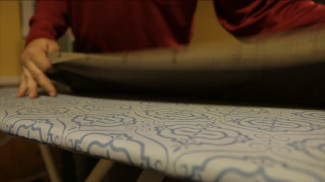hands place a shirt over an ironing board. - ironing board stock videos & royalty-free footage