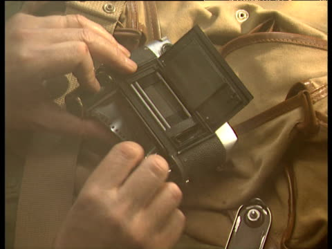 Hands place film into camera on top of rucksack then wind film before removing camera