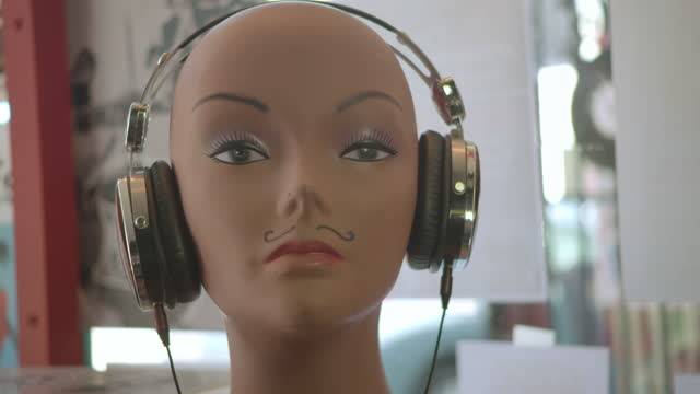 CU. Hands place headphones on head of mannequin display in modern record store.