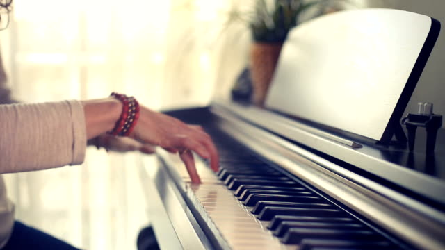 stockvideo's en b-roll-footage met hands playing the piano keys with no music sheet in a magical light - una sola mujer