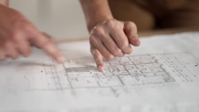 PAN Hands pointing out details on the construction plan