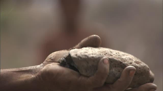 hands pound rocks together in kenya. - 潰された点の映像素材/bロール