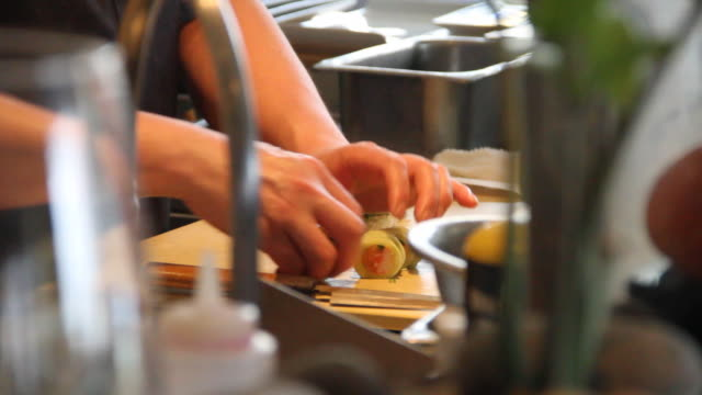 hands preparing sushi on cutting board - japanese food stock videos & royalty-free footage