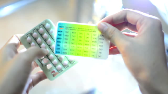 Hands Pressing Pill out of  Contraceptive