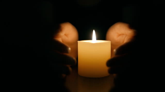 hands protecting burning candle candlelight in darkness - protection stock videos & royalty-free footage