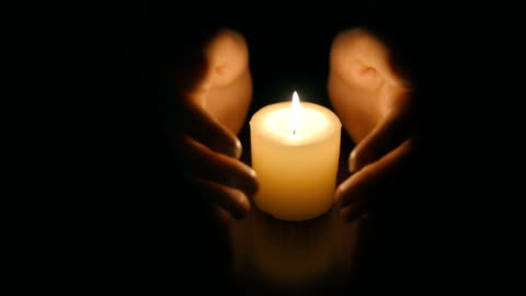 hands protecting burning candle candlelight in darkness - guarding stock videos & royalty-free footage