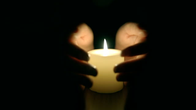 hands protecting burning candle candlelight in darkness - shielding stock videos & royalty-free footage