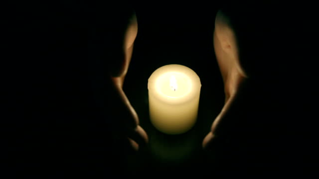 hands protecting burning candle candlelight in darkness - shield stock videos and b-roll footage