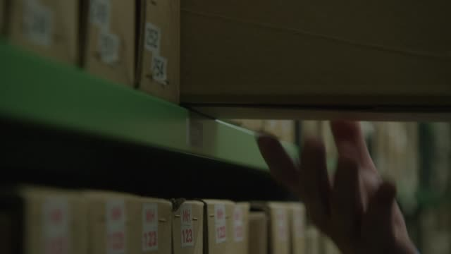 vídeos de stock, filmes e b-roll de hands pull out document storage boxes from shelving - bbc archives