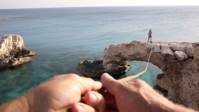 Hands pull rope tight to distant climber, above sea