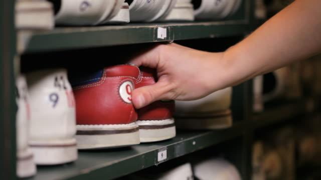 vídeos de stock, filmes e b-roll de hands put pair of bowling shoes back on a shelf - sapato de boliche